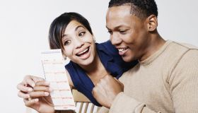 Excited couple looking at lottery ticket