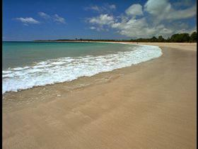 HA LS of ocean waves gently lapping onto a beach./Fiji