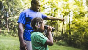 Father and daughter watching with binoculars in forest eco camp