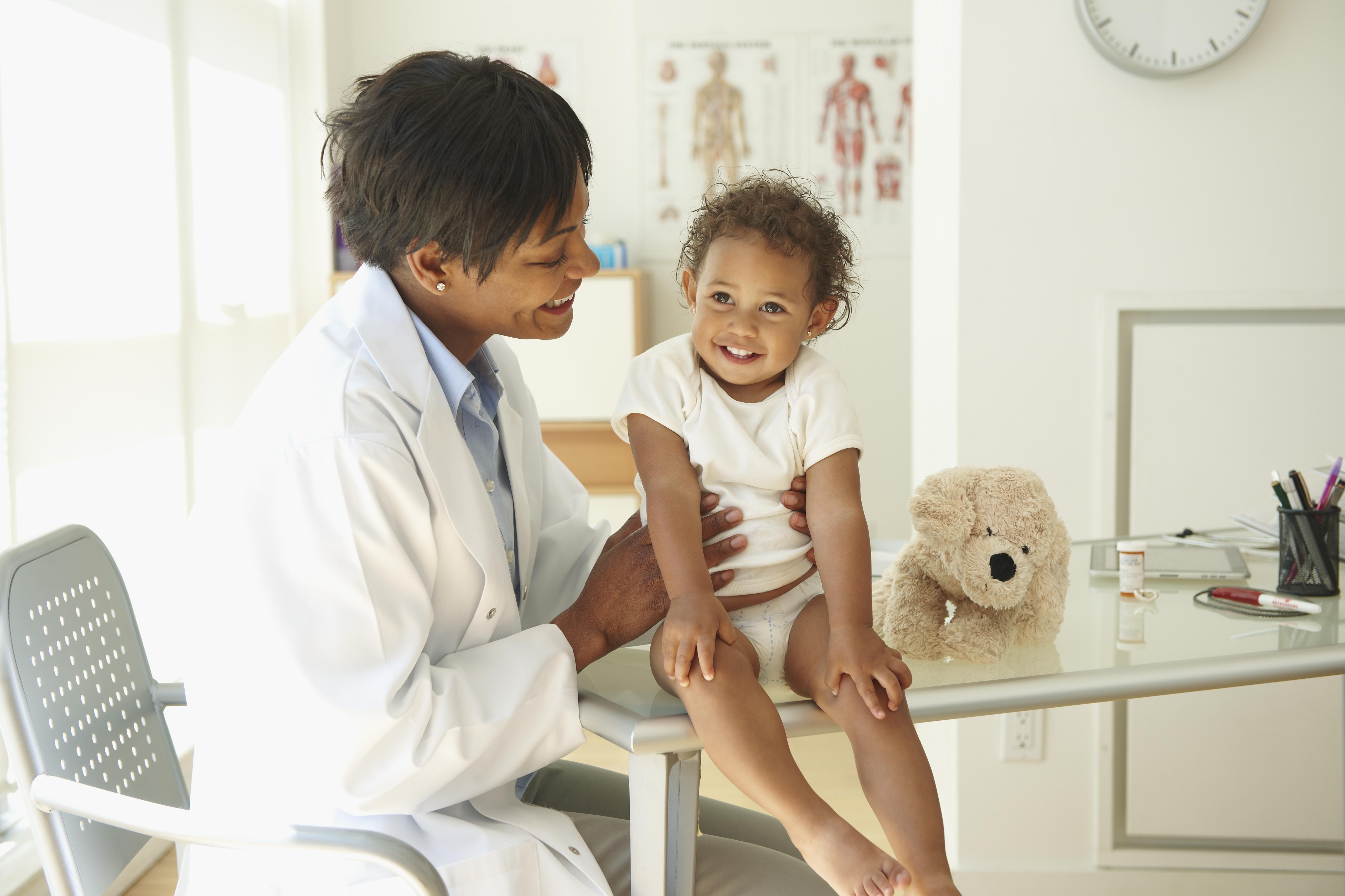 Doctor examining baby in doctor's office