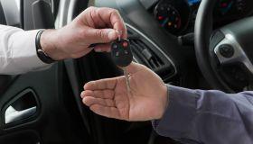 Hispanic car salesman handing keys to customer
