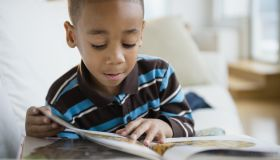 African American boy reading book on sofa