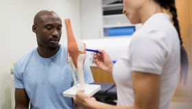 Physical therapist explaining knee model to patient