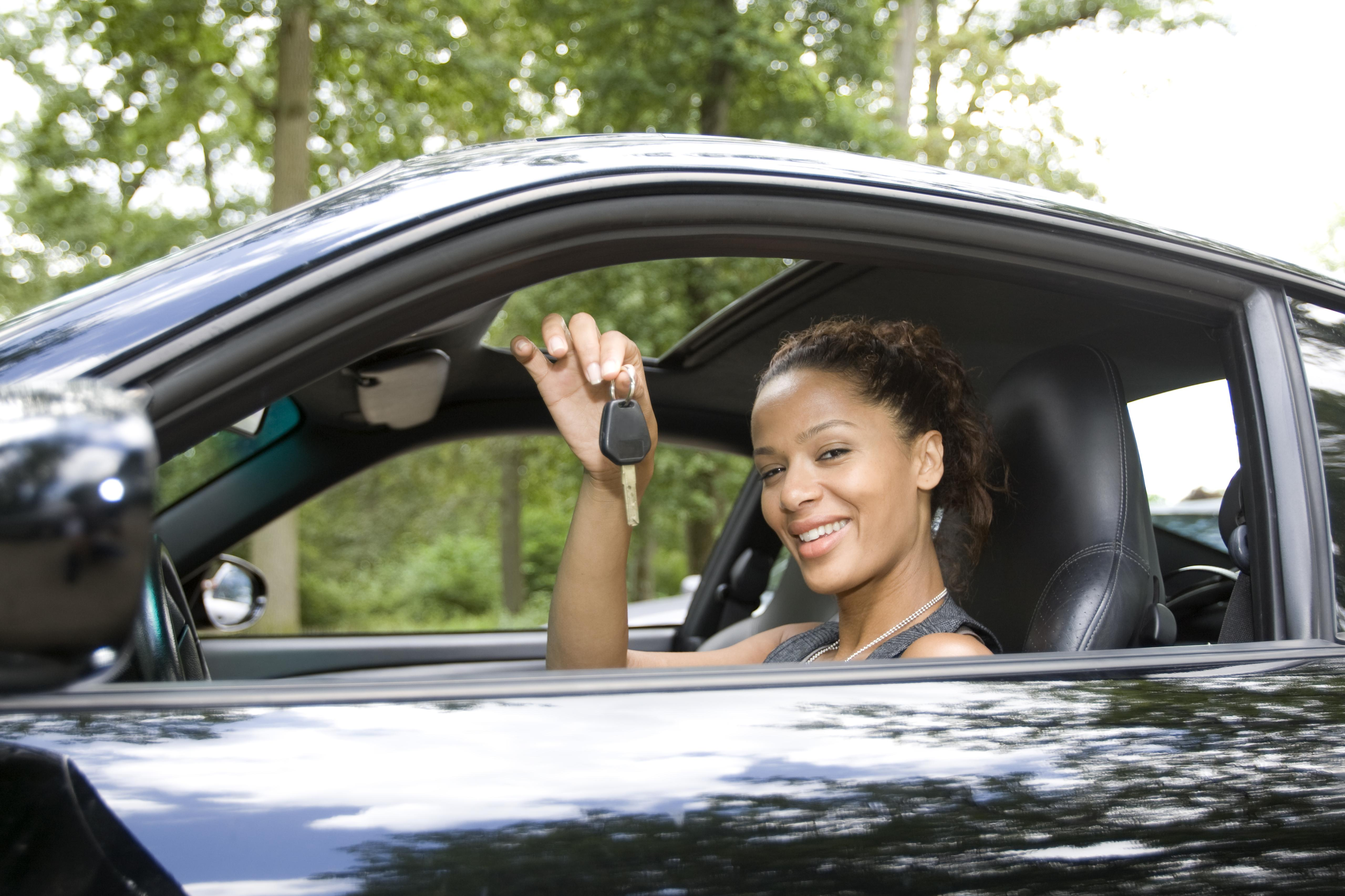 Woman holding key of a new car