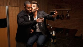 Gay couple drinking wine in kitchen and taking self-portraits