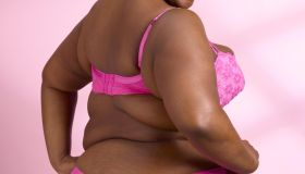 Overweight woman on pink background