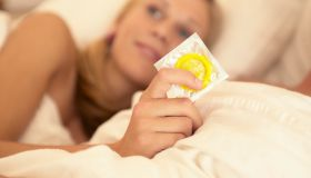 Teen girl holding condom