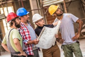 Architect explaining building plans to a group of construction workers