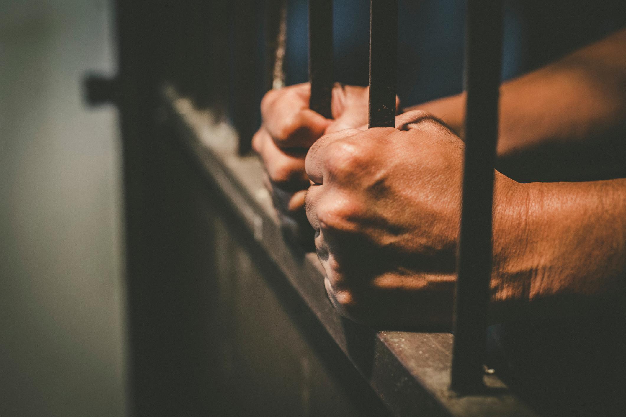 Cropped Hands Of Male Prisoner Holding Prison Bars