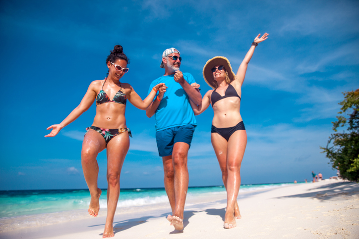 Mature Man and Two Young Women Enjoying Together on a Beach