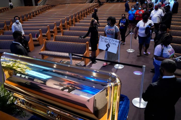 Mourners Pass By The Casket